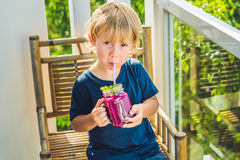 Der Junge hält Smoothies von einer Drachefrucht mit einem tadellosen Blatt und einem Trinkhalm stockfotos