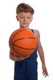 Der Junge hielt einen Basketballball eine eine Hand Lizenzfreie Stockfotos