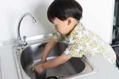 Der Junge hilft der Mutter, die Hausarbeit zu tun, indem er ein Glas und einen Teller wäscht stockfotografie