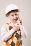 Der Junge im Bausturzhelm sprechend am Telefon Stockfoto