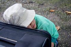 Der Junge im Hut schläft und lehnte sich am Koffer, der auf den Zug auf der Reise wartet lizenzfreie stockfotografie