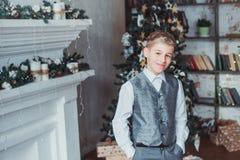 Der Junge im Wohnzimmer im Hintergrund des Weihnachtsbaums Kinder kleideten festlich an lizenzfreie stockfotos