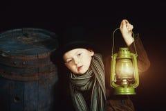 Der Junge im Zylinder hält eine Kerosinlampe stockfotografie