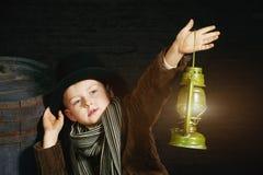 Der Junge im Zylinder hält eine Kerosinlampe stockfotos