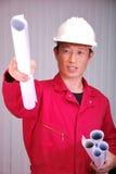 Der junge Ingenieur, die Arbeitskraft in der roten Uniform Stockfoto