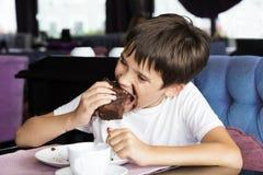 Der Junge isst ein großes Stück des Kuchens Lizenzfreie Stockbilder