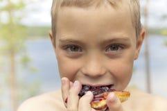 Der Junge isst Pfannkuchen mit Blaubeeremarmelade. stockfoto