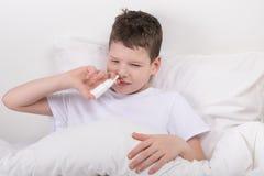 Der Junge ist im Bett, seine Nase ist stickig, er einnimmt die Medizin nasal stockbilder