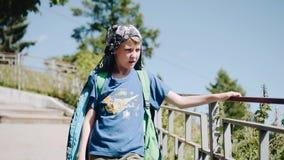 Der Junge in der Jacke kommt entlang auf die Promenade, Griffe auf die Schiene Sonniger Tag stock video