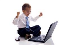 Der junge Junge, der als Geschäftsmann gekleidet wird, arbeitet an Laptop Stockfotos