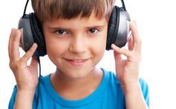 Der junge Junge hält die Kopfhörer an Stockbilder
