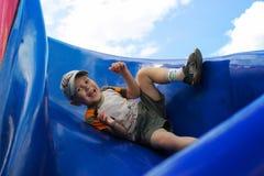 Der Junge in der Kappe, die auf das blaue Kind-` s Dia schiebt stockfotos