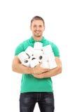 Der junge Kerl, der ein Bündel Toilettenpapier hält, rollt Lizenzfreies Stockfoto