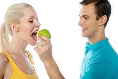 Der junge Kerl, der ihre Freundin bildet, essen einen Apfel lizenzfreies stockbild