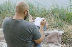 Der junge Kerl schreibt in ein Notizbuch lizenzfreie stockfotos