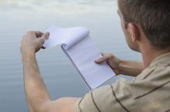 Der junge Kerl schreibt in ein Notizbuch lizenzfreie stockfotografie
