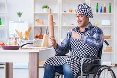 Der junge Koch mit der Rolle, die Teigmahlzeit vorbereitet Lizenzfreies Stockfoto