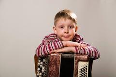 Der Junge kreuzte seine Arme und lehnte sich auf dem Akkordeon Lizenzfreie Stockfotografie