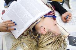 Der junge Kursteilnehmer schläft auf Büchern Stockfotos
