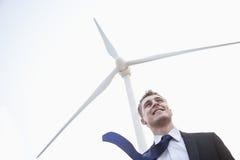 Der junge lächelnde Geschäftsmann, der neben einer Windkraftanlage steht, Bindung brennt im Wind durch Stockfotografie