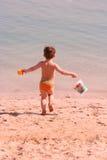 Der Junge läuft, um zu wässern Stockfotos