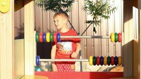 Der Junge lernt zu zählen Das Kind spielt auf dem Spielplatz stock footage