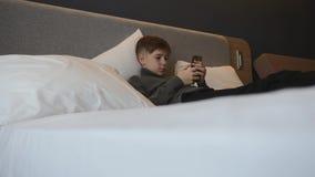 Der Junge liegt auf dem Bett mit einem Smartphone in seinen Händen Kommunikation und Spiele auf dem Smartphone stock video footage