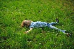 Der Junge liegt in einem dichten grünen Gras auf Rasen Stockfotos