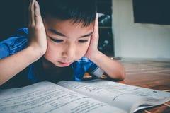 Der Junge liest das Buch für, die Prüfung vorzubereiten auf diesem kommenden Montag stockfotos
