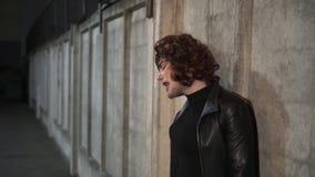 Der junge lustige Kerl, der wie Frau, tragende schwarze Kleidung und Perücke gekleidet wird, singt Außenseite stock footage