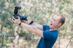 Der junge männliche Kerl, der erhalten wurde, erschrak von der DSLR-Kamera, die es in seinen Händen am Sommertag hält Lustiges Bi stockbilder