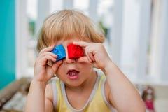 Der Junge macht Augen von bunten Kind-` s Blöcken Netter Kleinkindjunge mit den Gläsern, die mit vielen bunten Plastikblöcken her Stockbilder