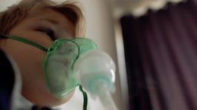Der Junge macht Einatmung beim Sitzen auf dem Bett Einatmungsmaske auf dem Gesicht des Patienten stock footage