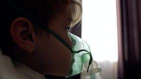 Der Junge macht Einatmung zu Hause auf dem Bett gegenüber von dem Fenster stock footage