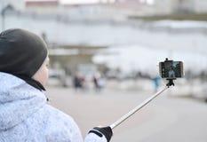 Der Junge macht selfie am Telefon mit selfie Stock auf Hintergrund des Anblicks stockfotos