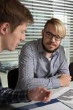 Der junge Manager ist zu den Details sehr aufmerksam Lizenzfreie Stockfotos