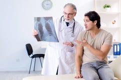 Der junge Mann, der alten m?nnlichen Doktorradiologen besucht lizenzfreies stockbild