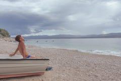 Der junge Mann, der auf Boot auf Kieseln ein Sonnenbad nimmt, setzen auf den Strand Stockfotos