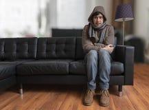 Der junge Mann, der auf Couch sitzt, fühlt sich zu Hause kalt lizenzfreies stockfoto