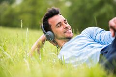 Der junge Mann, der auf dem grünen Gras liegt, hören die Musik und der Blick bei einer Seite stockfoto