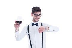 Der junge Mann betrachtet seine Uhr lächelnd und feiernd Lizenzfreie Stockfotos