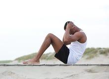 Der junge Mann, der auf dem Strandhandeln trainiert, sitzen ups Stockfoto