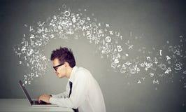 Der junge Mann, der auf Laptop-Computer Alphabet schreibt, beschriftet weg fliegen Stockfoto