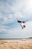 Der junge Mann, der auf Sand springt Lizenzfreies Stockfoto