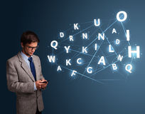 Der junge Mann, der auf Smartphone mit High-Techem 3d schreibt, beschriftet das Kommen Lizenzfreie Stockbilder