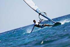 Der junge Mann, der den Wind spritzt surft innen, vom Wasser Lizenzfreies Stockbild