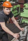 Der junge Mann, der an der alten Fabrik auf Installation von equi arbeitet Stockbild