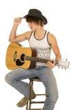 Der junge Mann, der eine Gitarre mit Cowboyhut spielt, sitzen Lizenzfreie Stockbilder