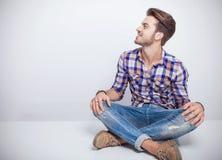Der junge Mann, der eine weiße Tabelle mit seinen Beinen sitzt, crosed Lizenzfreie Stockbilder