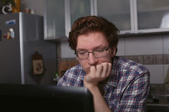 Der junge Mann, der an einem Laptop sitzt und denkt an das Lösen von Problemen stockfotografie